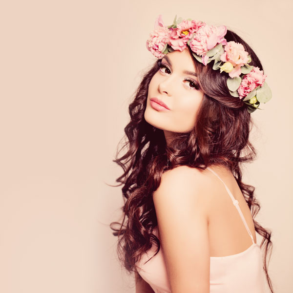 Young Woman With Curly Hair And Flowers
